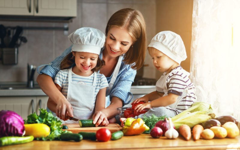 A mom and her two kids are prepping food in the kitchen for supper while following the Dietproof ™ program
