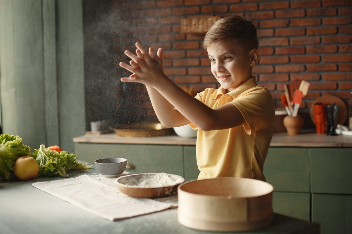 young boy in the kitchen getting ready to make flour