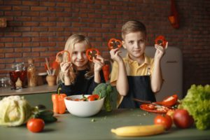 Kids cutting up vegetables in the kitchen