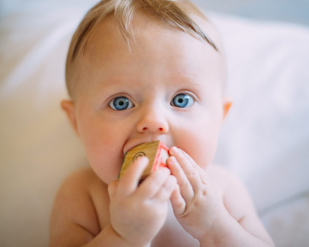 blue eyed baby chewing on a block